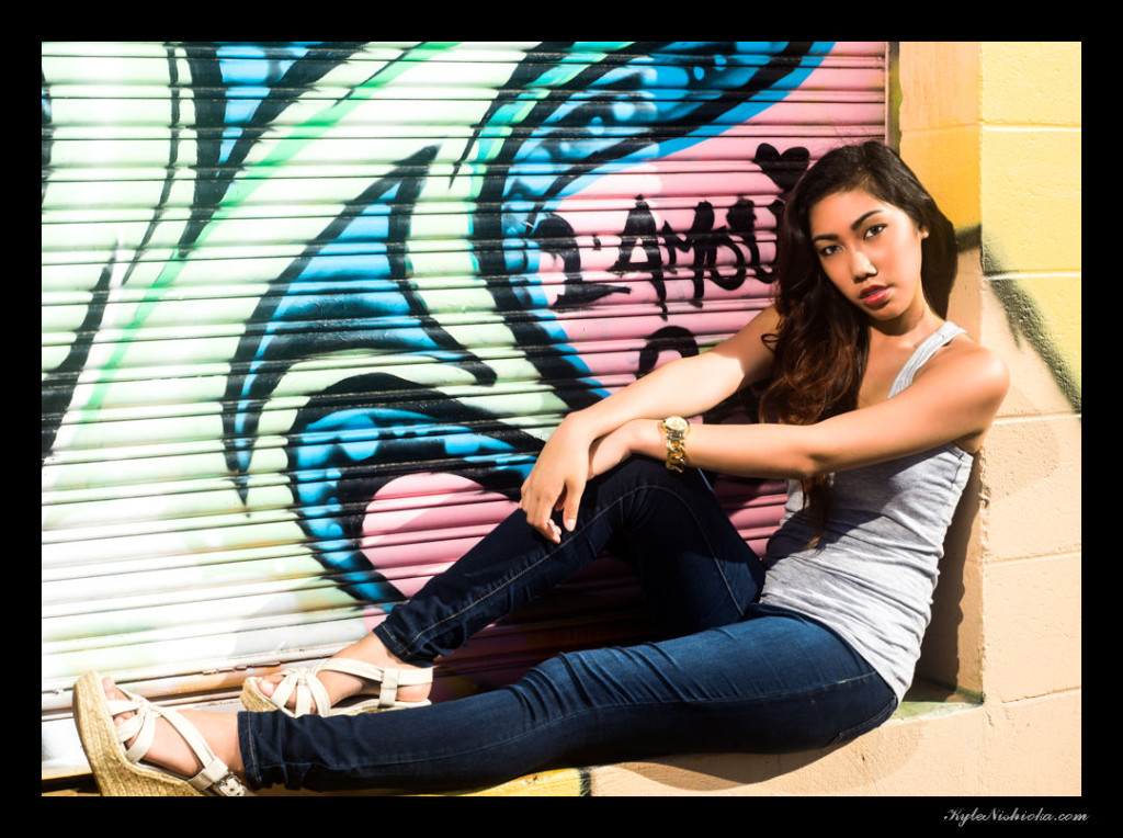 Maelea sitting posing in front of grafitti